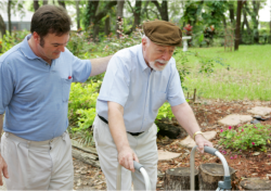 man assisting an old man to walk